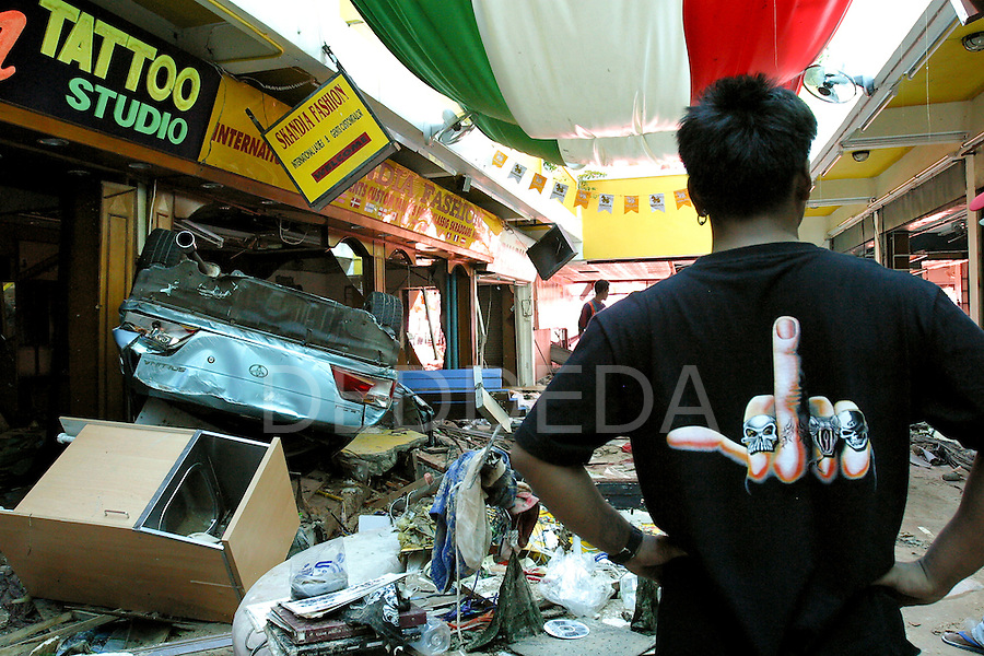 A tatoo artist examines the devastation to his shop, and other shops, after tsunamis hit Patong Beach on Phuket Island, Thailand. On December 26, 2004, a major earthquake generated tsunamis that ravaged coastlines from Southeast Asia to Africa. Approximately 275,000 people were killed and tens of thousands were left homeless, making it one of the deadliest natural disasters in modern history.