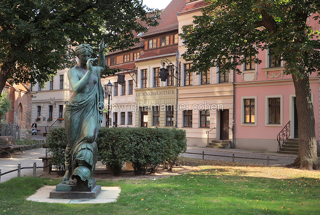 Bronze statue of Clio, muse of history and writing, 1876, by Albert Wolff, on Nikolaikirchplatz, in the Nikolaiviertel near the Nikolaikirche or St Nicholas Church, Berlin, Germany. The townhouses behind are reconstructions of the original Baroque houses. Picture by Manuel Cohen