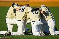 Several of the Wake Forest Demon Deacons baseball players huddle up for a prayer prior to the game against the North Carolina State Wolfpack at Wake Forest Baseball Park on March 15, 2013 in Winston-Salem, North Carolina.  The Wolfpack defeated the Demon Deacons 12-6.  (Brian Westerholt/Four Seam Images)