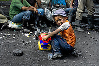 A child plays with a car toy while his mother is having a break in the mine of Muzo, Colombia, 21 April 2006. Despite of a persisting civil war conflict and related difficulties Colombia still produces 60 percent of world emerald production. Due to the special clarity and deep vivid green color, gemstones from Muzo are considered the most beautiful emeralds in the world. There have been thousands of treasure hunters coming to Muzo during last decades. They have been searching for a fortune, infatuated by so-callled green fever. The major part of guaqueros (emerald miners) spent long years in the hot and wet unhospitable jungle working hard, they contracted malaria or tropical diseases but they still kept their dream about magic green stone alive.