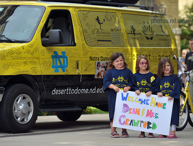 """Three girls hold a sign welcoming College of Science Dean Greg Crawford and his wife Renate back to campus after their """"Desert to Dome"""" bike ride from Tucson, AZ to South Bend, IN to promote the Notre Dame-Parseghian Foundation partnership...Photo by Matt Cashore/University of Notre Dame"""