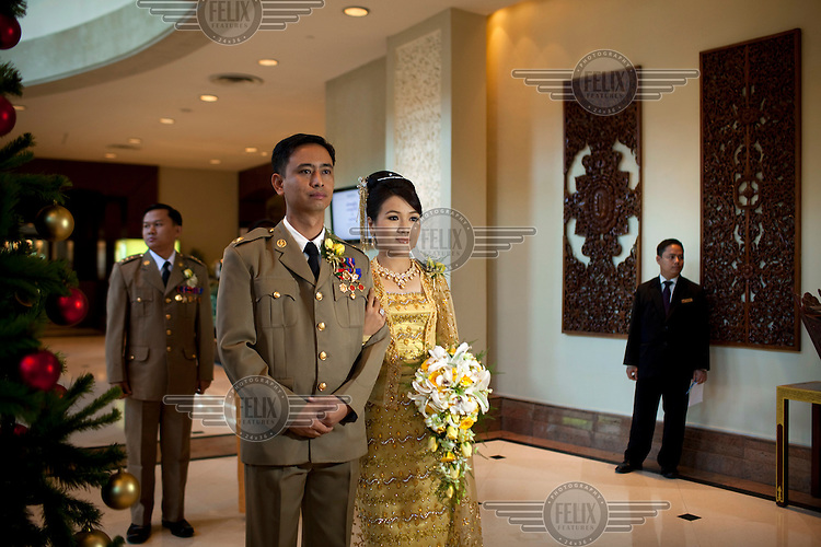 Major Win Min Tun (left) and Ma Aye Aye Mu (right) prepare to enter their wedding reception at a luxury hotel in Yangon.