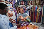 A shopkeeper shows traditional Tunisian clothing to a tourist from the United States in the Medina (old city) in Tunis.