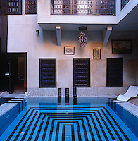 A swimming pool with a geometric tile pattern dominates the central courtyard of this riad