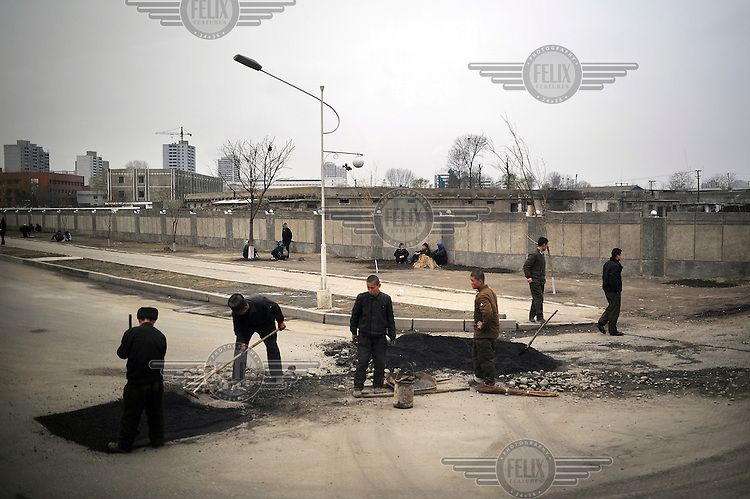 Construction workers repair a road in central Pyongyang.