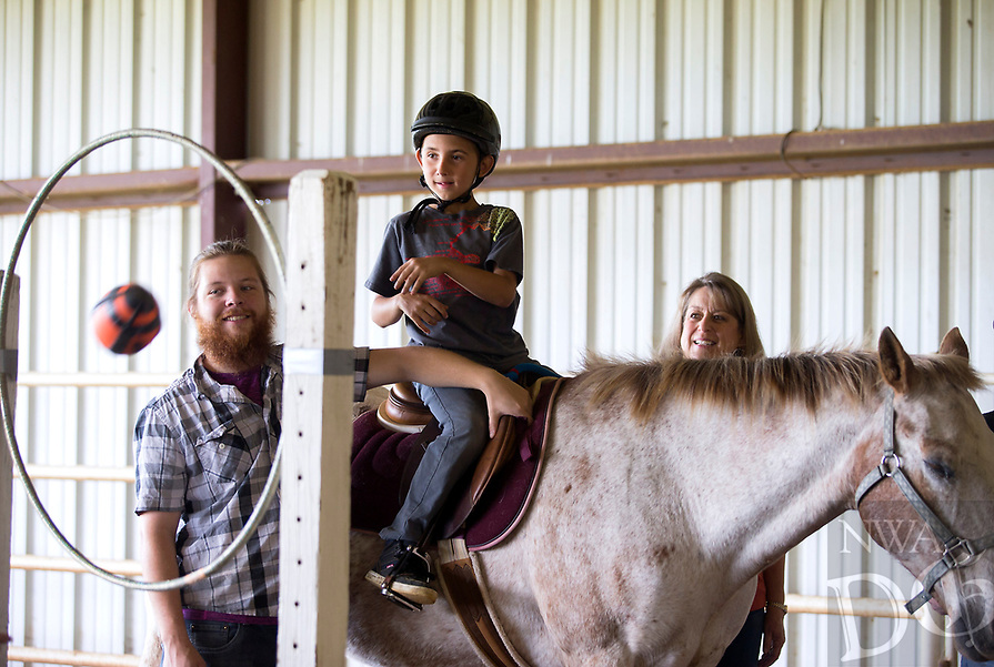NWA Democrat-Gazette/JASON IVESTER<br /> Volunteers help as Hayden Vicent, Grimes Elementary second-grader, tosses a ball through a hoop from a horse in the arena Tuesday, May 2, 2017, during the Special Olympics equestrian event at Horses for Healing in Bentonville. Thirty students from Rogers schools participated in the theraputic riding event.