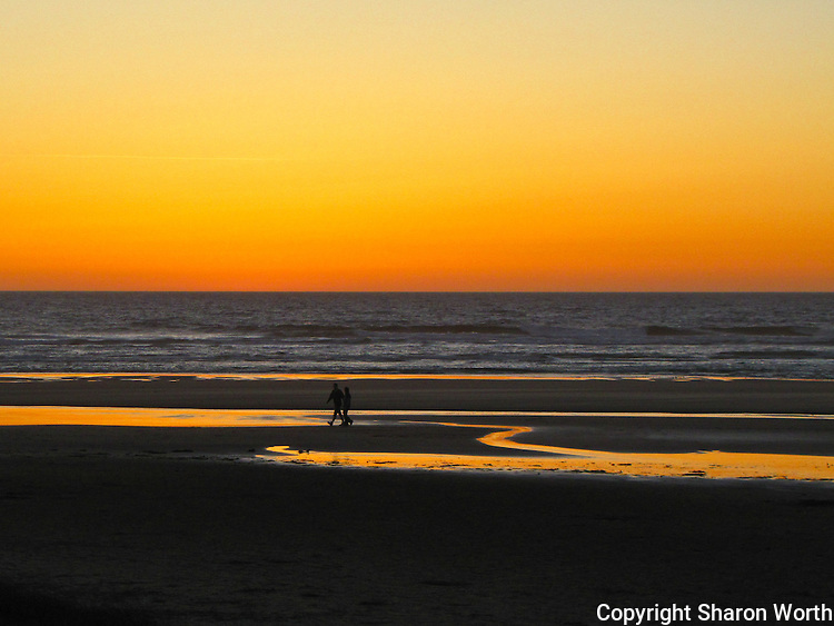 A couple enjoys an end-of-the-day stroll along Haceta Beach at sunset.