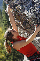 Female climber climbing overhanging rock face, Banff, Banff National Park, Alberta, Canada