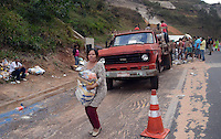 BRUMADINHO MG, 25 Julho 2013 - Um acidente com um caminhao carregado com cestas basicas que ia de BH a Pouso Alegre MG e perdeu o freio no trajeto, interrompu uma faixa da Rodovia Fernao Dias na altura do KM 526 na região de Brumadinho, MG nesta quinta  feira, 25.  na foto Mulher aproveita a situacao e foge com uma cesta basica (FOTO: ALAN MORICI / BRAZIL PHOTO PRESS).