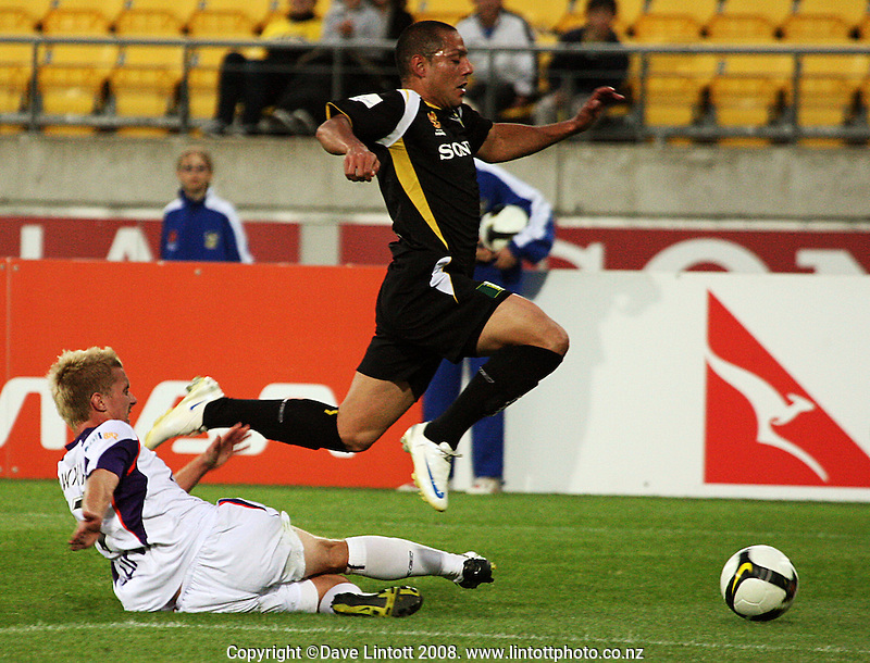Leo Bertos hurdles James Downey's tackle during the A-League football match between the Wellington Phoenix and Perth Glory at Westpac Stadium, Wellington, New Zealand on Saturday, 13 December 2008. Photo: Dave Lintott / lintottphoto.co.nz