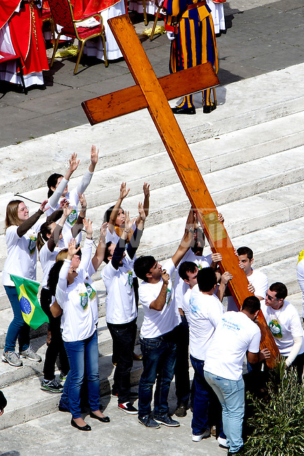 Brazilian young people carry the Cross of the World Youth Day to give it to Polish young people at the end of Palm Sunday Mass at St. Peter's Square on April 13, 2014 in Vatican