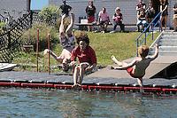Sascha Bialon, Antonin und Raimund Schirdewan sind die Ersten Badegäste im Wasser bei der Eröffnung der Badesaison am Badesee Walldorf