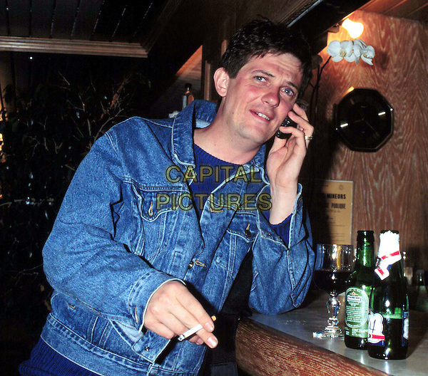 MATTHEW WRIGHT..Ref: 4916..smoking, on mobile phone, denim jacket, pub, half length, half-length..www.capitalpictures.com..sales@capitalpictures.com..©Capital Pictures