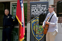 NWA Democrat-Gazette/DAVID GOTTSCHALK  Sgt. Craig Stout, with the Fayetteville Police Department, listens to Ryan Porter, Monday, May 15, 2017, as he sings during the Northwest Arkansas Law Enforcement Memorial at the Town Center in Fayetteville. Area law enforcement departments participated in the memorial that recognized officers from Northwest Arkansas who died in the line of duty.