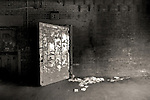 A steel door with peeling paint and brick wall