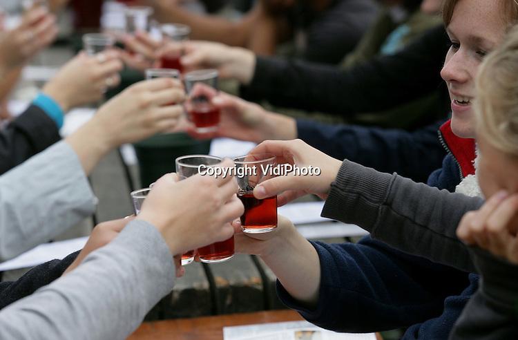 Foto: VidiPhoto..WAGENINGEN - In Biologische Wijngaard Wageningse Berg Wordt eigenaar Jan Oude Voshaar zaterdag geholpen door vijftig studenten van de Wageningen Universiteit bij de oogst van zijn blauwe druiven (Regent). Als beloning krijgen de vrijwilligers na afloop een wijnproeverij. Steeds meer Nederlandse wijnboeren stappen over op het telen van biologische druiven. Volgend jaar produceert de helft van de Nederlandse wijnboeren biologische wijn. In geen enkel ander land is dat percentage zo hoog. De wijnen van Jan Oude Voshaar behoren tot de Nederlandse top. Bij de wijnkeuring van dit jaar heeft hij opnieuw diverse prijzen in de wacht gesleept.