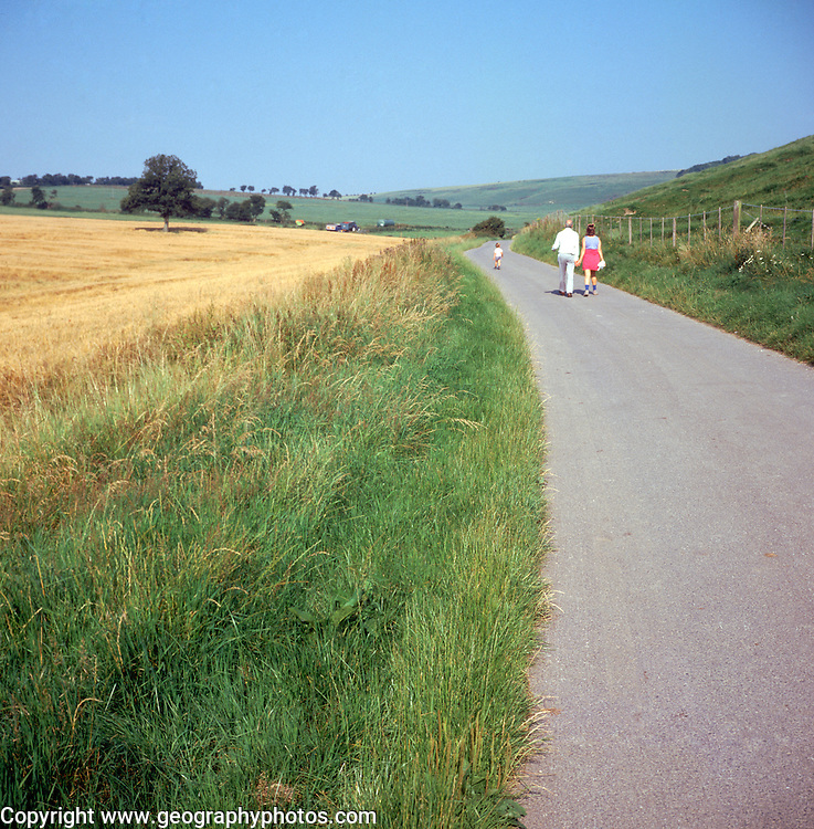 Father, daughter, child walk along country lane through chalk downland, Ramsbury, Wiltshire, England