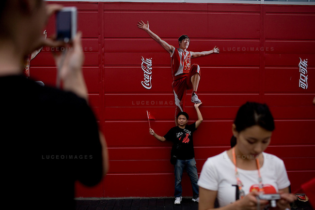 Locals pose in front of China's Olympic hurdler Liu Xiang at the Coca-Cola building on the Olympic Green in Beijing, China on Thursday, August 21, 2008.  Kevin German