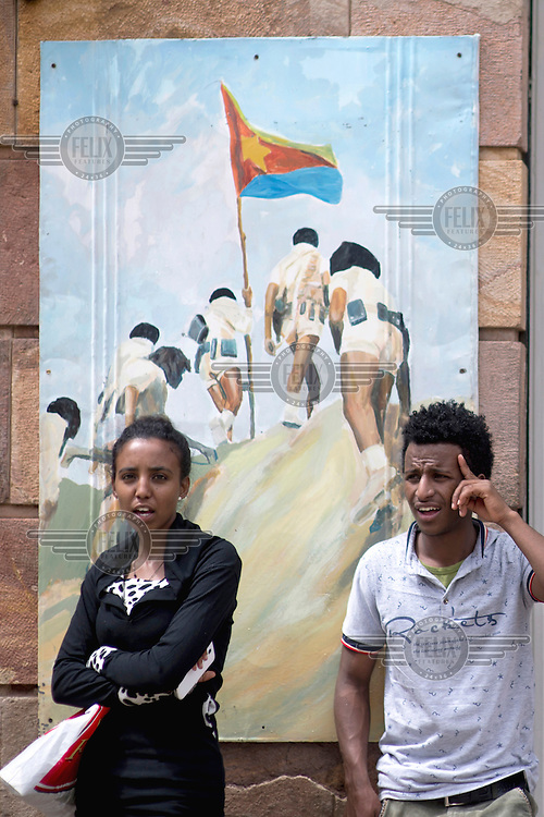 A man and a woman stand in front of a poster,  featuring the national flag, celebrating the independence of 1991.