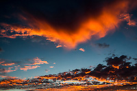 Two distinct sunset-orange cloud formations frame a patch of blue sky above San Francisco Bay at sunset.