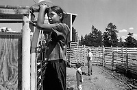 A girl hangs on the bullriding gates at the annual Lincoln Rodeo in Lincoln, MT in June 2006.  The Lincoln Rodeo is an open rodeo, which means competitors need not be a member of a professional rodeo association.
