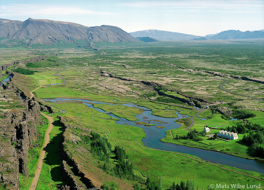 Þingvellir / Thingvellir, Almannagjá / Almannagja earthquake rift in foreground left. River Öxará / Oxara and the priesters fram and church right in picture. Aerial..Þingvallahreppur