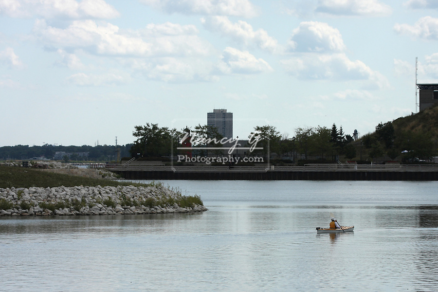 A female kayaker kayaking the Milwaukee Harbor in front of the Summerfest grounds