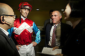 An unidentified jockey speaks with guests at the Hong Kong Jockey Club's Happy Valley racecourse.