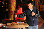 Bao-jhong Yi-min Temple, Kaohsiung -- Temple custodian preparing an incense coil.