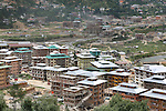 Modern town construction with traditional style contemprary architecture for a growing population, outskirts of Thimpu, Bhutan..Bhutan the country that prides itself on the development of 'Gross National Happiness' rather than GNP. This attitude pervades education, government, proclamations by royalty and politicians alike, and in the daily life of Bhutanese people. Strong adherence and respect for a royal family and Buddhism, mean the people generally follow what they are told and taught. There are of course contradictions between the modern and tradional world more often seen in urban rather than rural contexts. Phallic images of huge penises adorn the traditional homes, surrounded by animal spirits; Gross National Penis. Slow development, and fending off the modern world, television only introduced ten years ago, the lack of intrusive tourism, as tourists need to pay a daily minimum entry of $250, ecotourism for the rich, leaves a relatively unworldly populace, but with very high literacy, good health service and payments to peasants to not kill wild animals, or misuse forest, enables sustainable development and protects the country's natural heritage. Whilst various hydro-electric schemes, cash crops including apples, pull in import revenue, and Bhutan is helped with aid from the international community. Its population is only a meagre 700,000. Indian and Nepalese workers carry out the menial road and construction work.