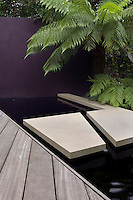 Large sandstone stepping stones cross the pond which is flanked by decking, an aubergine rendered wall and ferns