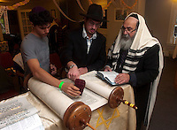 """Rabbi Yaakov Rapoport, Director of Chabad House Lubavitch at Syracuse University, and his son Mendy Rapoport, help Ben Romy read from the Torah during a morning service for Hoshana Rabbah. Hoshana Rabbah is the seventh day of Sukkot and is considered the final day of the divine """"judgment"""" in which the fate of the new year is determined.  Photo by James R. Evans ©"""