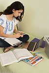 18 year old teenage girl at home, in bedroom at home, doing homework, multitasking, using laptop computer and cell telephone
