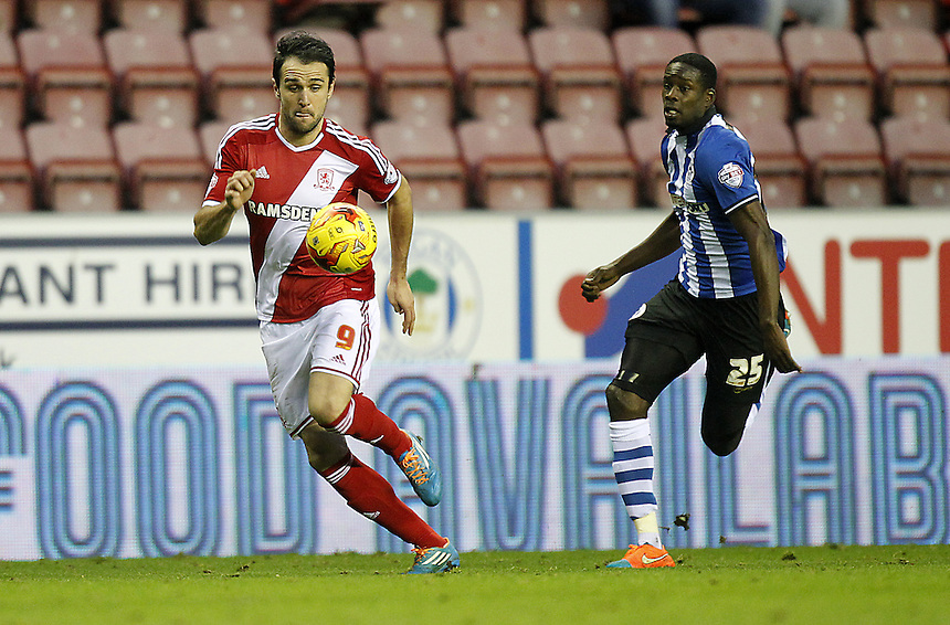 Middlesbrough's Kike is chased by Wigan Athletic's Leon Barnett<br /> <br /> Photographer Mick Walker/CameraSport<br /> <br /> Football - The Football League Sky Bet Championship - Wigan Athletic v Middlesbrough - Saturday 22nd November 2014 - DW Stadium - Wigan<br /> <br /> &copy; CameraSport - 43 Linden Ave. Countesthorpe. Leicester. England. LE8 5PG - Tel: +44 (0) 116 277 4147 - admin@camerasport.com - www.camerasport.com