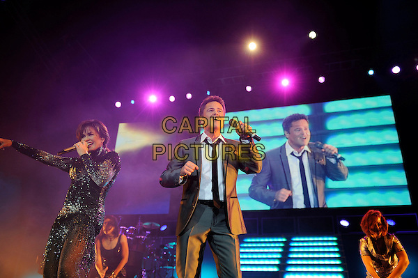 Donny & Marie Osmond.Live at the O2 Arena, London, England..January 20th 2013.on stage in concert live gig performance performing music half length grey gray suit black dress sparkly singing brother sister siblings family hand arm  singing  .CAP/MAR.© Martin Harris/Capital Pictures.