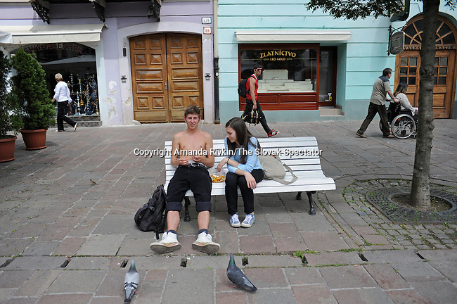 Locals picnic on a bench on a warm day on the Main Street in Kosice, Slovakia on May 30, 2010.