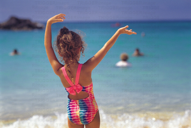 A young girl waves her hands in the air while spending summer vacation on a beach