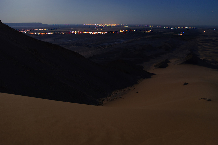 The desert plateau around Al-Qasr, Dakhla Oasis, under a full moon - the lights of Al-Qasr and Mut in the distance