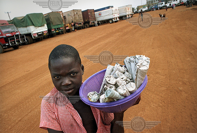 A small boy selling peanuts to truck drivers at a border crossing parking bay.