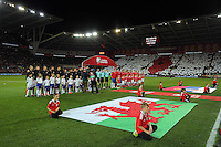 Wales and Serbia players line up for the national anthems while a red poppy is seen in the stand behind for Remembrance Day during the 2018 FIFA World Cup Qualifier between Wales and Serbia at the Cardiff City Stadium, Wales, UK. Saturday 12 November 2016