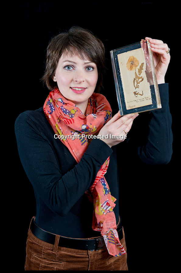 BNPS.co.uk (01202 558833)<br /> Pic: RachelAdams/BNPS<br /> <br /> ***Please use full byline***<br /> <br /> Auctioneer Amy Brennan holds the acrylic-encased poppy.<br /> <br /> <br /> The oldest surviving poppy from the bloody battlefields of the First World War has emerged for sale almost 100 years after it was first picked.<br /> <br /> The vivid red flower was taken from the front-line trenches of Arras in northern France by 17-year-old British soldier Private Cecil Roughton in 1916.<br /> <br /> The poppy is thought to be the oldest in Britain and one of only two that survived from the First World War.<br /> <br /> It is expected to sell for £1,000 when it goes under the hammer at Duke's Auctioneers in Dorchester, Dorset.