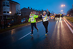 "A cuople, representing some wine-bar workers, carries a baton on the 19th ""Korrika"" at dawn, on a rainy morning. Irun (Basque Country) March 22, 2015. The ""Korrika"" is a relay course, with a wooden baton that passes from hand to hand without interruption, organised every two years in a bid to promote the basque language. The 19th Korrika will run over 11 days and 10 nights, crossing many Basque villages and cities, totalling some 2300 kilometres. Some people consider it an honour to carry the baton with the symbol of the Basques, ""buying"" kilometres to support Basque language teaching. The ""Korrika"" this year ends in Bilbao on March 29. (Gari Garaialde / Bostok Photo)"