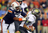 Jan 10, 2011; Glendale, AZ, USA; Oregon Ducks quarterback Darron Thomas (right) is tackled by Auburn Tigers defensive tackle Nick Fairley (90) during the first quarter of the 2011 BCS National Championship game at University of Phoenix Stadium.  Mandatory Credit: Mark J. Rebilas-