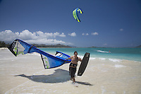 Kite surfer carrying his equipment rig (kite and board) down Kailua Beach