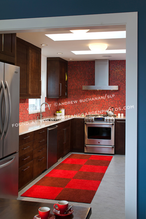 Blue dining room walls complement the bright red tile backsplash in this bold, contemporary kitchen remodel. This image is available through an alternate architectural stock image agency, Collinstock located here: http://www.collinstock.com