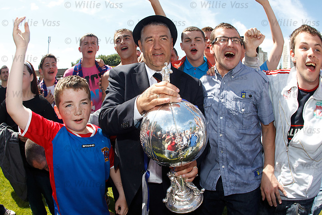Irvine Meadow's manager Chris Strain gets his hands on the junior's Cup Winners Cup as the fans celebrate