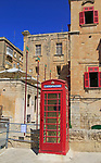 Red telephone box booth in historic city centre of Valletta, Malta