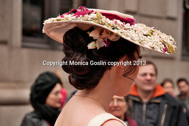 A woman wears a large flat hat with white flowers on it to the Easter Parade in New York City on Fifth Avenue