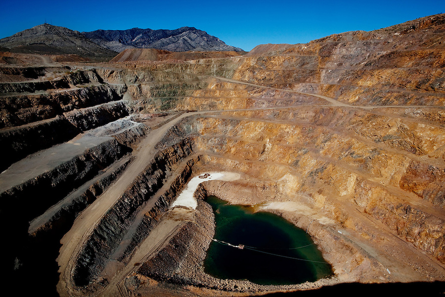 """Mountain Pass, California, November 15, 2010 - A view of the open-air mine at Mountain Pass, owned by Molycorp Minerals, which mines rare earth elements. According to Scott Honan, an Environmental Manager for Molycorp, the grey rock in unusable minerals, while the brown and pink rock contains rare earth minerals. """"When we resume mining operations, we will be able to mine 2 tons of earth per day, with about an 8% yield of rare earth,"""" Honan added. Rare earth elements - there are 17 in all - are crucial for many current technologies, including mobile phones, wind turbines, hybrid cars, laptops and military hardware, such as Army tank navigation systems and Navy radars. Uranium prospectors discovered the mine at Mountain Pass in 1949 and it became the dominant producer of rare earth elements until the 1990s when pressure from other producers began to drive prices down. That along with a number of leaks of radioactive water during transmission into a evaporation lake 13 miles away and state regulators delaying operating permits forced the mines closure in 2002. Though mining ceased, some processing of already mined elements continued. Molycorp was purchased by Unocal in the 1970s, which in turn was purchased from Chevron. In 2008 it's long-time chief executive, Mark A Smith, purchased in from Chevron with the help of several private equity firms. The company raised $500 million in an effort to reopen the mine, which will include expanding and modernizing the current facilities as well as incorporating newer technologies to make mining the radioactive material more environmentally safe and adding a natural gas power plant to help reduce its need to buy more expensive and less reliable energy from Los Angeles.  ."""