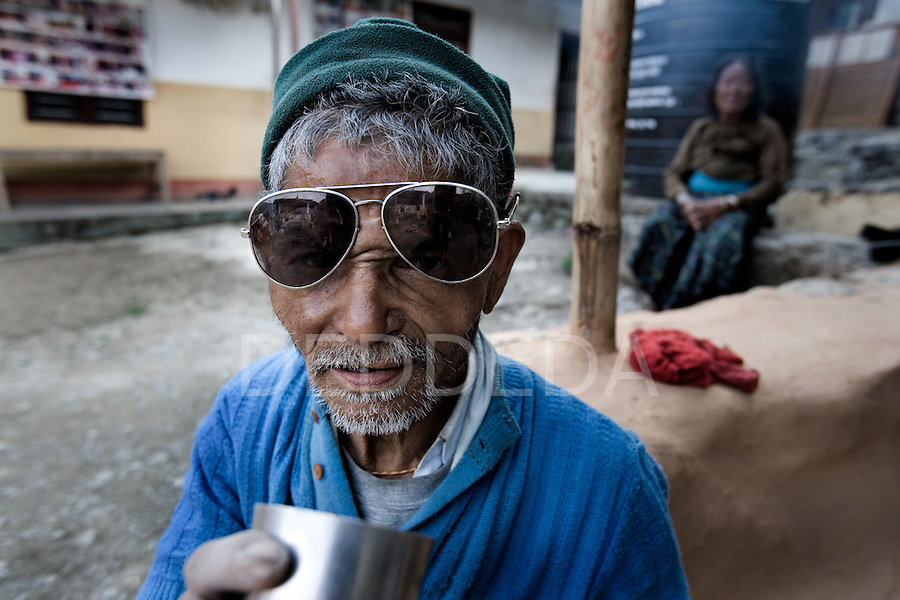 """An elderly man drinks tea at an """"Aged Shelter"""" in Pokhara, Nepal, a place for seniors to live who have no other family members to look after them. The shelter has no running water, cooking is done over a fire because they can not afford to buy gas for a stove, there are no nurses or doctors available, no heating, and no medication."""